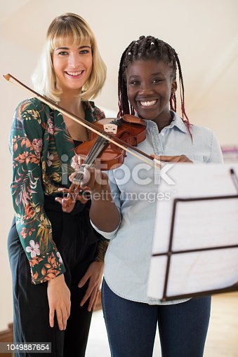 istock Portrait Of Female High School Teacher With Student Playing Violin In Music Lesson 1049887654