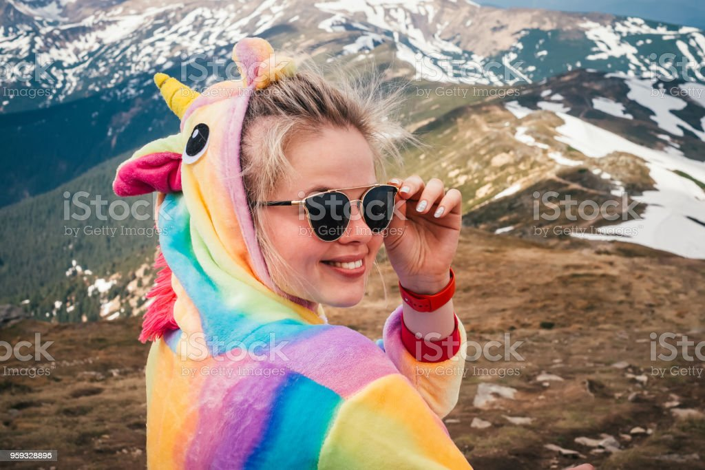 Portrait of female hiker in a unicorn costume in mountains stock photo