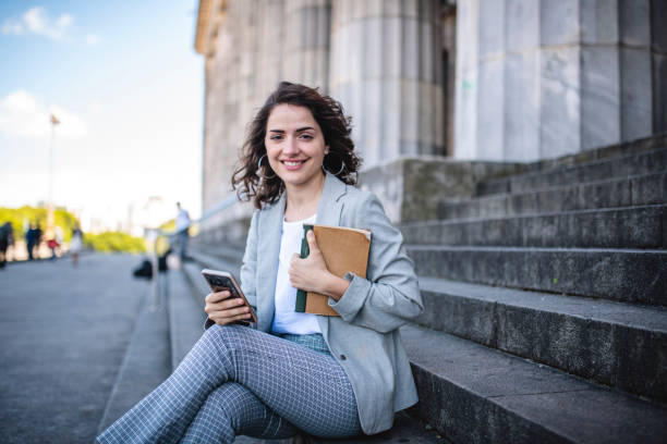 Portrait of Female Law Student with Book and Smart Phone stock photo