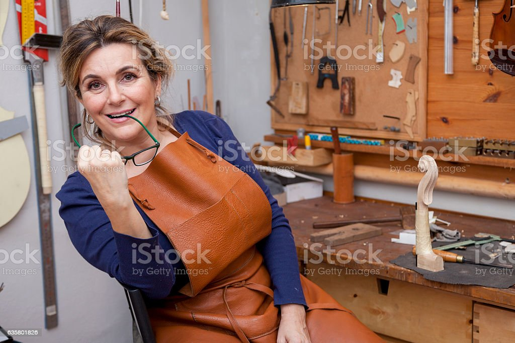portrait of female mature violin maker while testing the violins stock photo