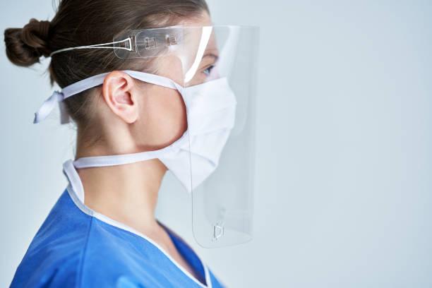 Porträt der Ärztin mit Schutzmaske und Gesichtsschutz – Foto