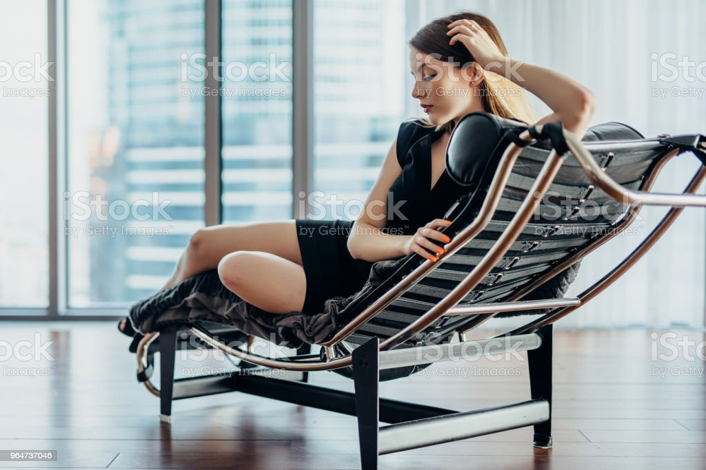 Portrait of female model wearing short black dress and high heels relaxing on chair royalty-free stock photo