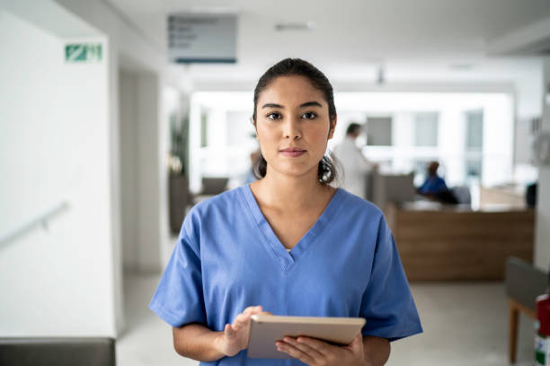 Portrait of female nurse using tablet at hospital Portrait of female nurse using tablet at hospital nurses stock pictures, royalty-free photos & images