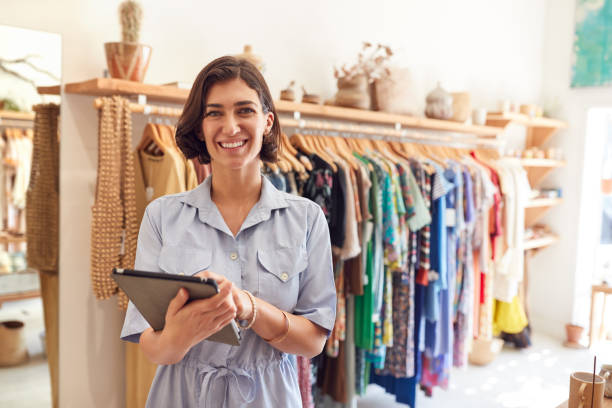Portrait Of Female Owner Of Fashion Store Checking Stock In Clothing Store With Digital Tablet stock photo