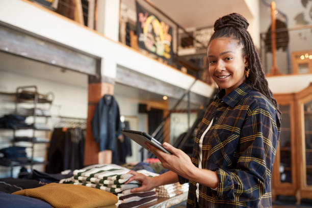 Portrait Of Female Owner Of Fashion Store Using Digital Tablet To Check Stock In Clothing Store stock photo