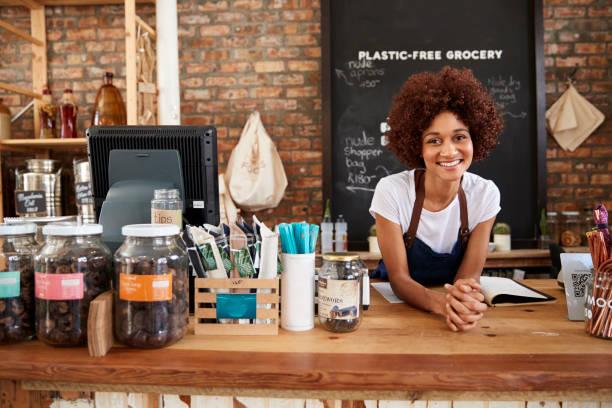 Retrato de mujer propietaria de plástico sostenible libre tienda de comestibles detrás de sales Desk - foto de stock