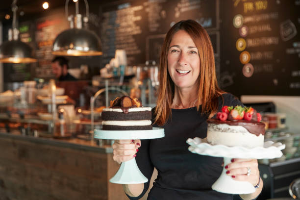 portrait of female owner with cakes on stands in coffee shop - panettiere foto e immagini stock