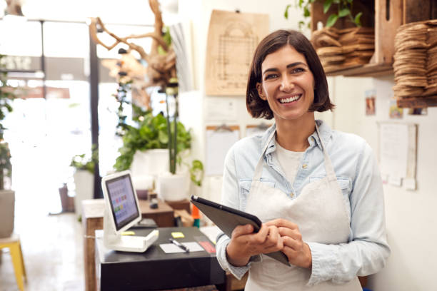 Portrait Of Female Owner With Digital Tablet Standing Behind Sales Desk Of Florists Store stock photo