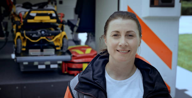 Portrait of female paramedic Female paramedic smiling into camera. ambulance staff stock pictures, royalty-free photos & images