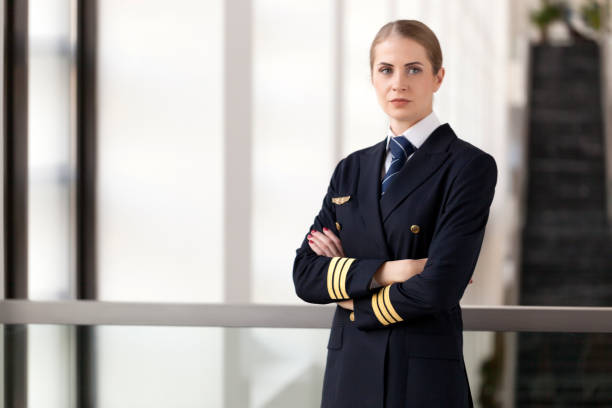 Portrait Of Female pilot standing at airport lobby stock photo