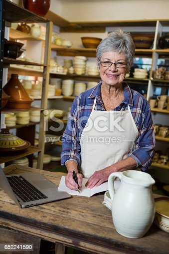 istock Portrait of female potter making note from laptop 652241590