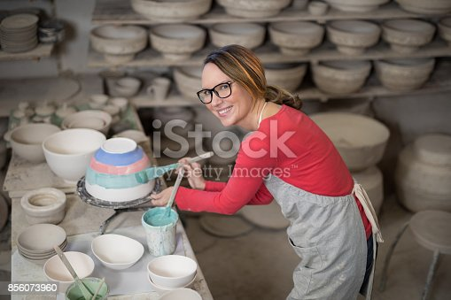 istock Portrait of female potter painting bowl 856073960