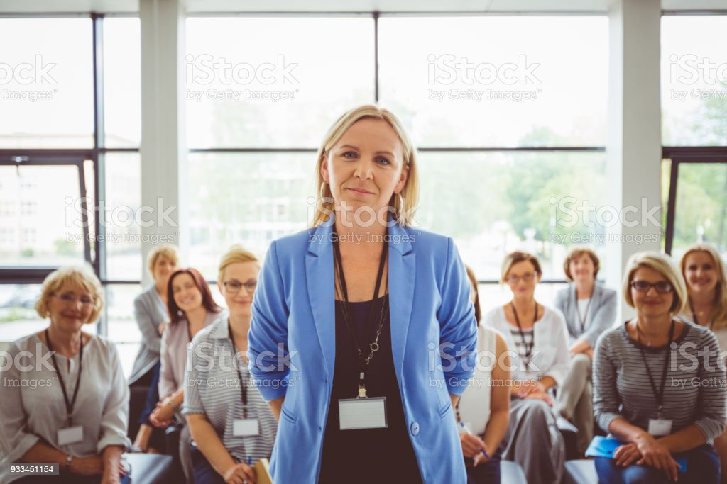 Portrait of female presenter with audience in background Portrait of smiling presenter with female audience in background. Beautiful businesswoman looking at camera. Adult Stock Photo