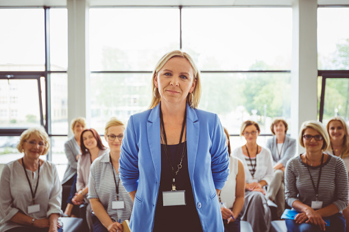 Portrait Of Female Presenter With Audience In Background Stock Photo - Download Image Now