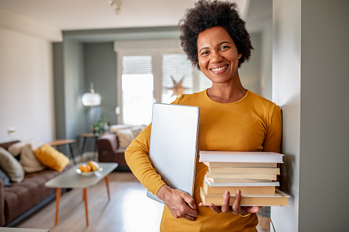 Portrait of woman holding books and laptop
