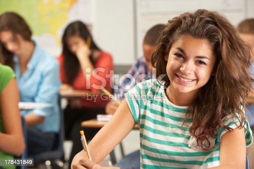 Portrait Of Female Pupil Studying At Desk In Classroom Smiling At Camera