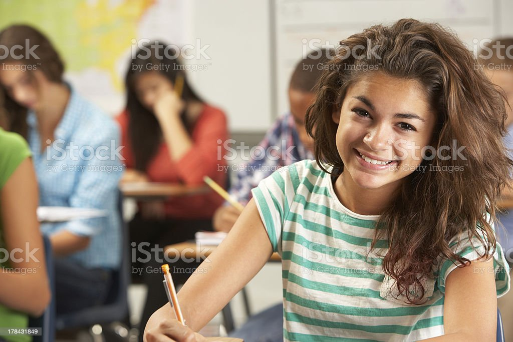 Portrait Of Female Pupil Studying At Desk In Classroom stock photo