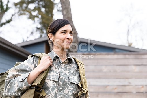 A portrait of a female soldier carrying her gear as she leaves her home for the deployment.