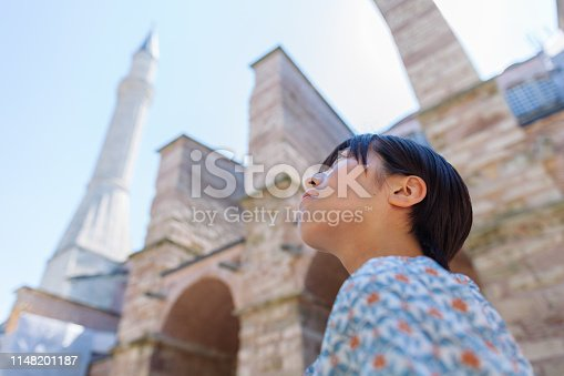 A portrait of a female solo traveler in front of a mosque museum.