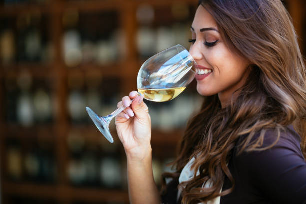Portrait of female sommelier smelling wine before tasting it at wine cellar stock photo