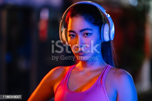 1071416330 istock photo Portrait of female sports person lit by neon lights at night 1186349007