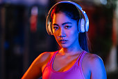 A portrait of a female sportsperson lit by near lights while listening to music with bluetooth wireless headphones.