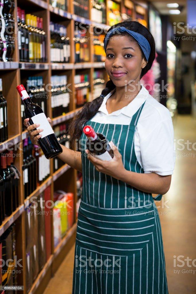 Portret van vrouwelijk personeel regelen van wijnflessen op plank foto