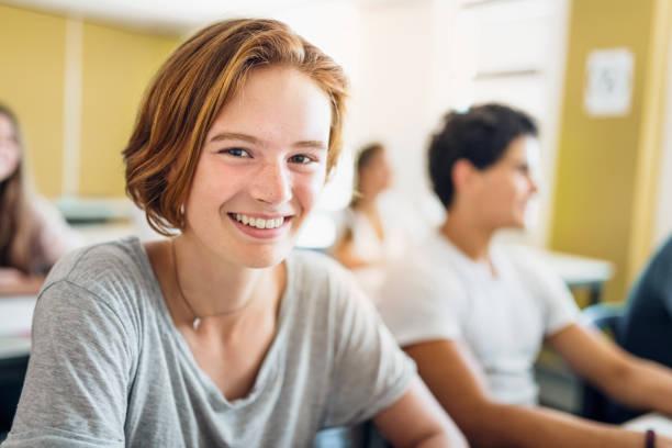 porträt von studentin lächelnd im klassenzimmer - 16 17 jahre stock-fotos und bilder
