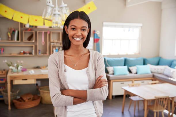 Portrait Of Female Teacher In Classroom At Montessori School stock photo