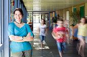 portrait of female teacher, leaning at corridor wall, running children in background
