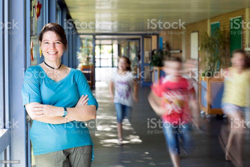 portrait of female teacher, leaning at corridor wall, running children in background stock photo