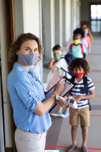 Portrait of female teacher wearing face mask with clipboard and temperature gun stock photo