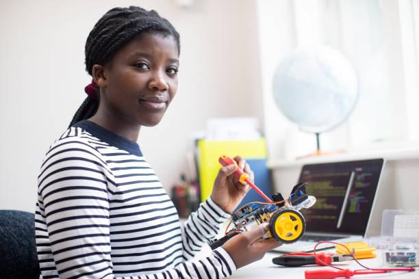 retrato de la alumna adolescente mujer edificio robot coche en la lección de ciencias - robótica fotografías e imágenes de stock