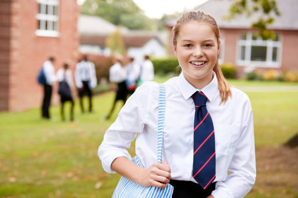 portrait of female teenage student in uniform outside buildings - private school stock photos and pictures