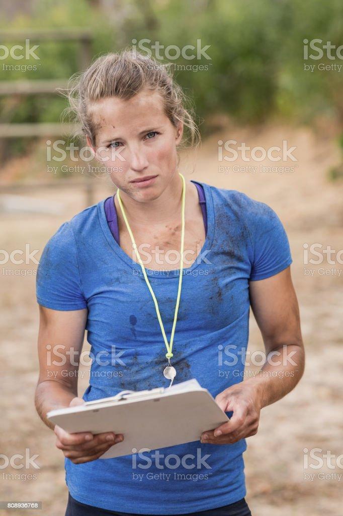 Porträt von weiblichen Trainer hält Zwischenablage im Hindernis-Parcours – Foto