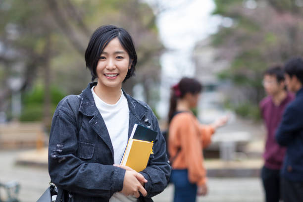 Portrait of female university student A portrait of a young Japanese female university student while her friends are talking to each others in the background. only japanese stock pictures, royalty-free photos & images