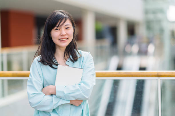 Portrait of female university student while holding textbook A portrait of a female university student while holding a textbook happily. japanese ethnicity stock pictures, royalty-free photos & images