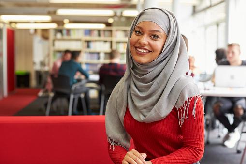 Portrait Of Female University Student Working In Library - Fotografie stock e altre immagini di Abbigliamento casual
