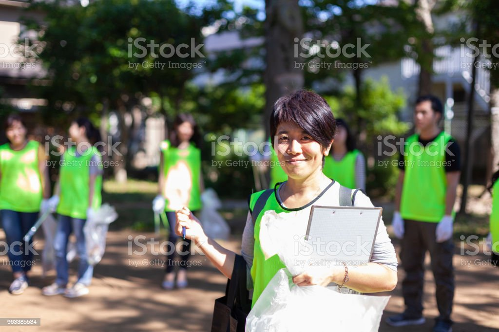 A portrait of a female volunteer group leader while the members are...