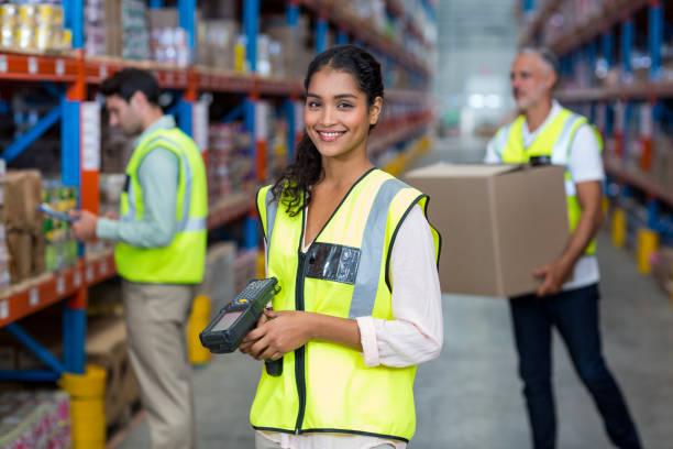 portret van vrouwelijke magazijnmedewerker permanent met barcodescanner - warehouse worker stockfoto's en -beelden