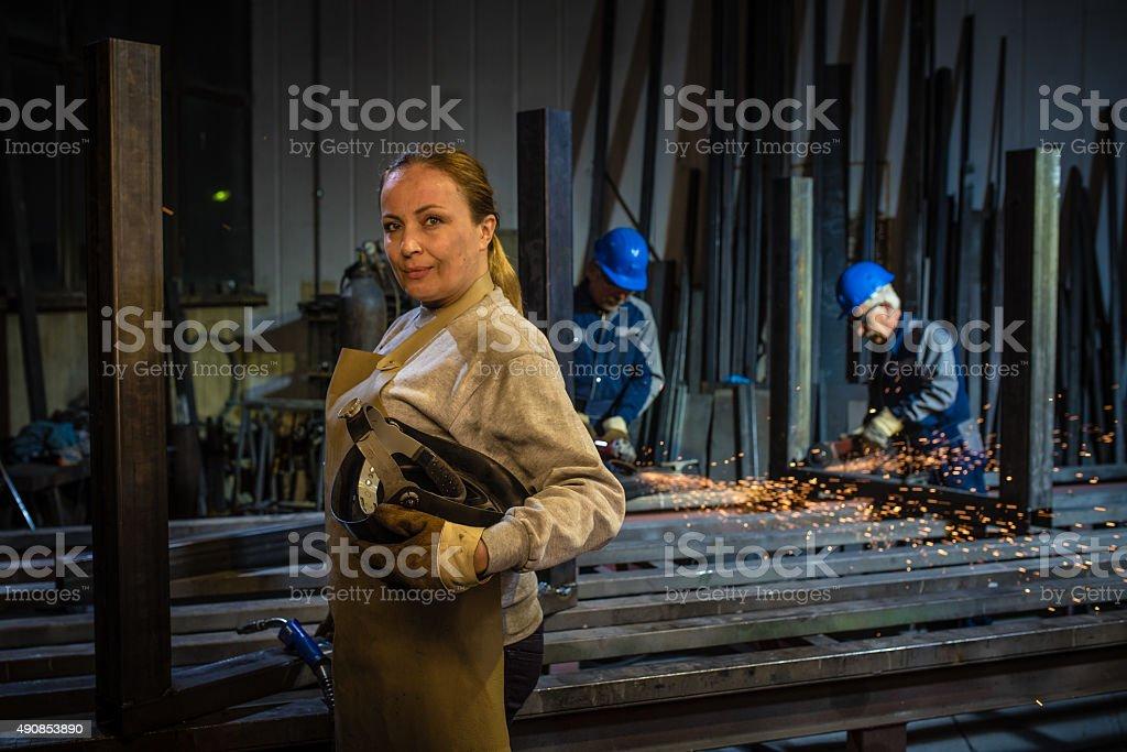 Woman standing with welding torch and welder\'s visor in workshop,...