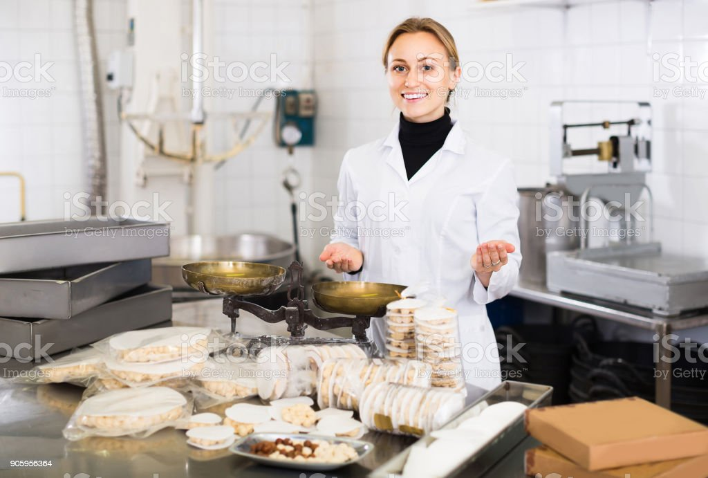 Portrait of  female with packing of turron in food factory stock photo