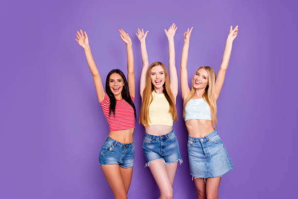 Portrait of festive cheerful girls with raised arms showing two fingers v-sign enjoying summer time together isolated in vivid violet background stock photo