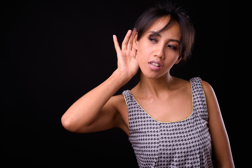 Portrait Of Filipino Woman Listening With Hands Cupped Behind Ear Against Black Background Stock Photo - Download Image Now