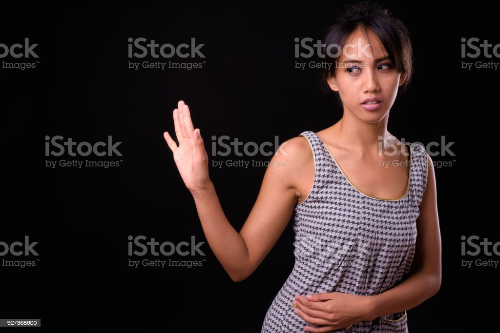 Portrait Of Filipino Woman Making Stop Gesture Against Black Background Studio Shot Of Woman From Philippines Against Black Background 25-29 Years Stock Photo