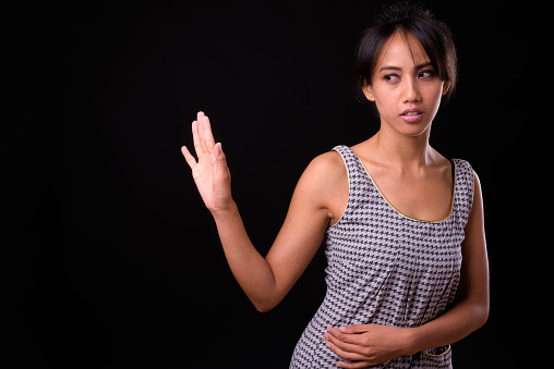 Portrait Of Filipino Woman Making Stop Gesture Against Black Background Stock Photo - Download Image Now