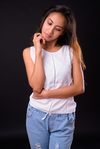 Portrait Of Filipino Woman Thinking Against Black Background Stock Photo - Download Image Now