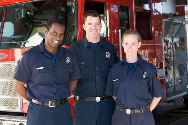 portrait of firefighters standing by a fire engine - firefighter stock photos and pictures