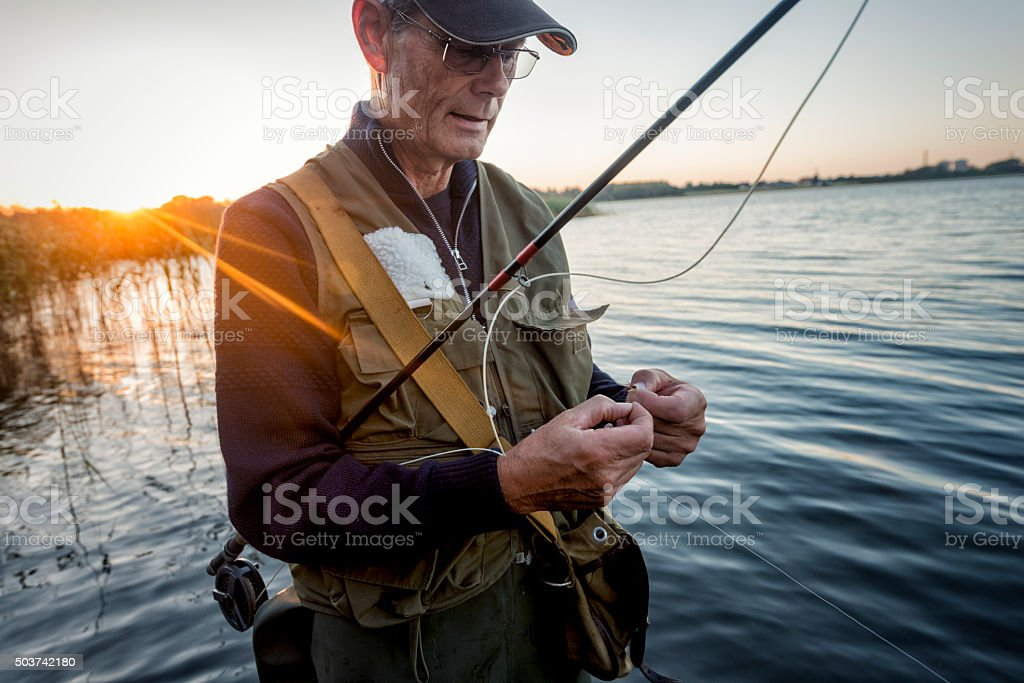 Portrait of Fisherman Tying a Fly on Stege Nor Denmark stock photo