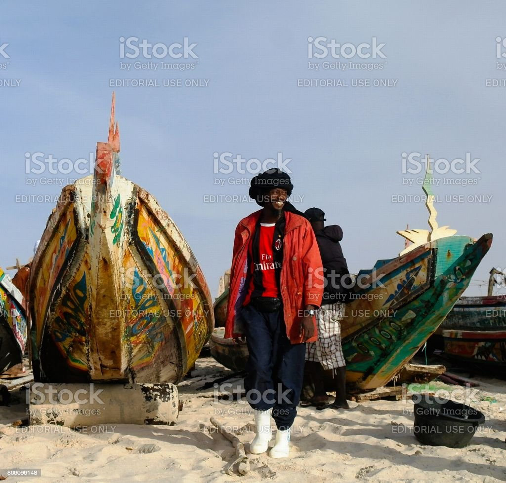 Portrait of fisherman with the boats at the beach of Nouakchott, Mauritania stock photo